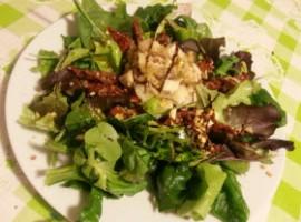 Insalata con pesce spada, foglie verdi , pomodori secchi e pistacchio