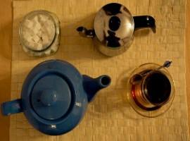 Teiera in ceramica, zollette zucchero, bollitore e tazza da té: una pausa té speciale