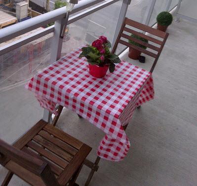 Tavolo con tovaglia a scacchi rossi e bianchi con mazzo fiori rossi e sedie su un patio di Maha via Flickr