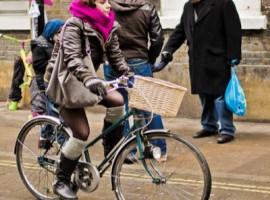 Ragazza in bici con sciarpa e guanti per sfidando il grande freddo