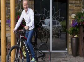 Uomo in bicicletta davanti a hotel