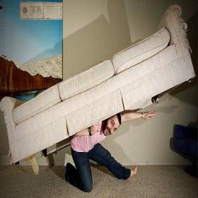 Un uomo con un sofa sulle spalle