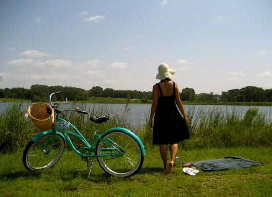 Donna e bicicletta sulle rive di un fiume