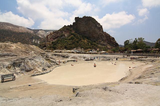 Alcune persone si immergono nei fanghi della pozza termale dell'isola di Vulcano