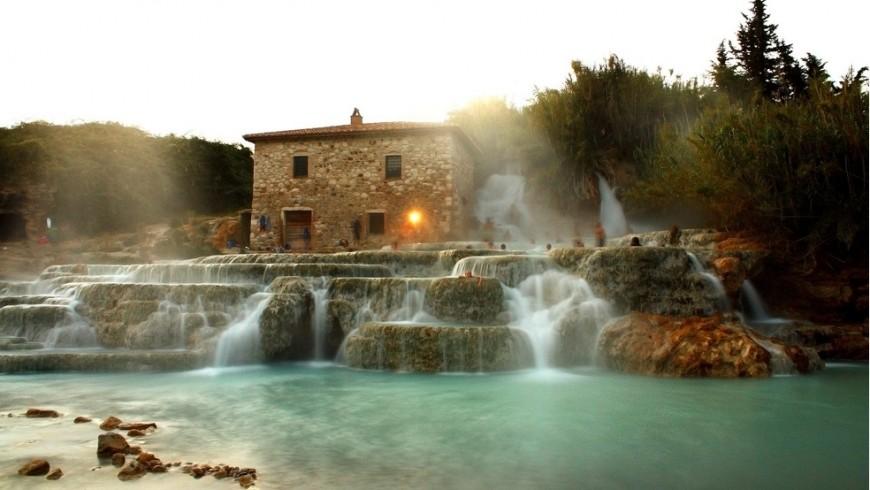 Davanti ad una casa in pietra, alcune cascatelle si gettano in un piccolo lago