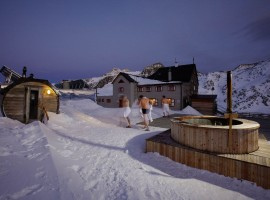 in un passaggio innevato, tra uomini con gli asciugamani si dirigono verso il rifugio; a sinistra si vede la sauna svedese, a destra la piscina (rifugio Bella Vista, BO)