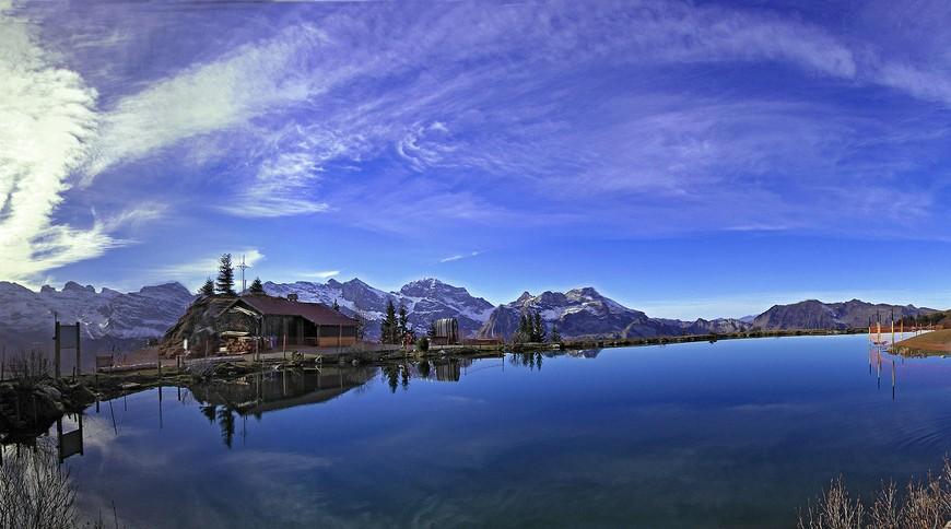 Il cielo si rifrette nel lago Härzlisee (Svizzera); sullo sfondo una baita e le catene montuose innevate