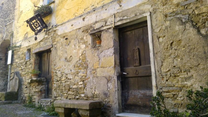 Edificio in pietra; la porta in legno reca un volto inciso e dal muro sporge (Colla Micheri, SV)