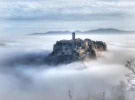 Civita di Bagnoregio, la città che muore vista da lontano immersa nella nebbia