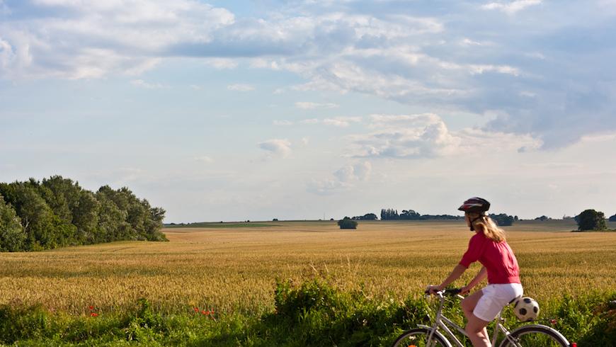 Donna in bici, circondata dalla natura