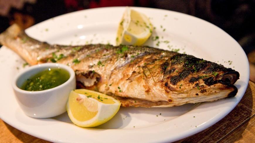 pesce ai ferri in un piatto con spicchi di limone e prezzemolo tritato