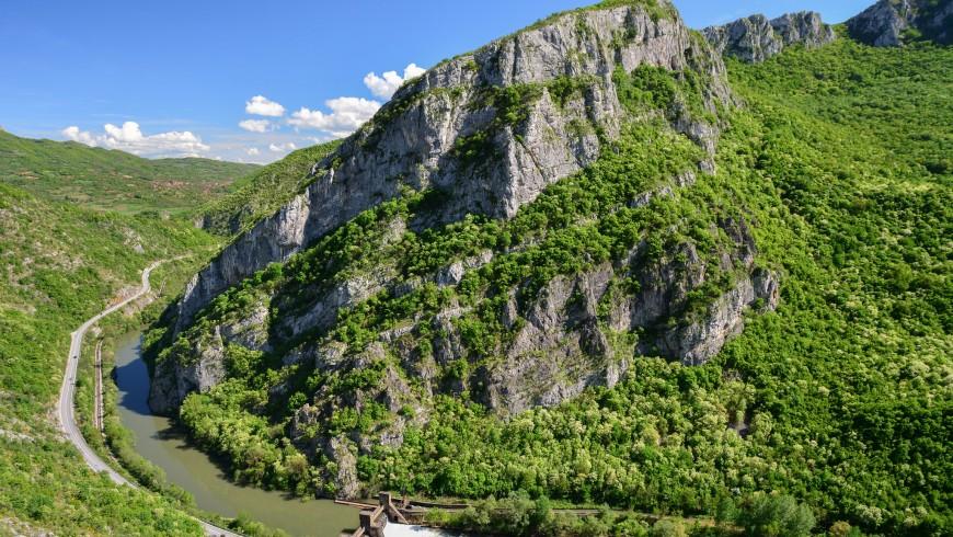 un fiume scorre tra rilievi rocciosi ricoperti di verdi boschi