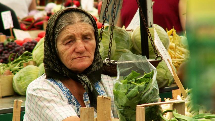 una signora anziana con un fazzoletto in testa vende verdura al mercato