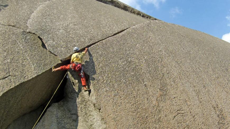 uno scalatore segue una fessura granitica arrampicando
