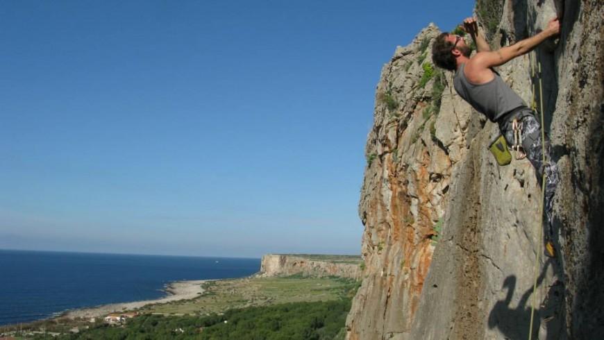 uno scalatore sulle rosse pareti con il mare alle spalle