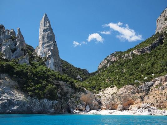 spiaggia con pareti di roccia e guglia
