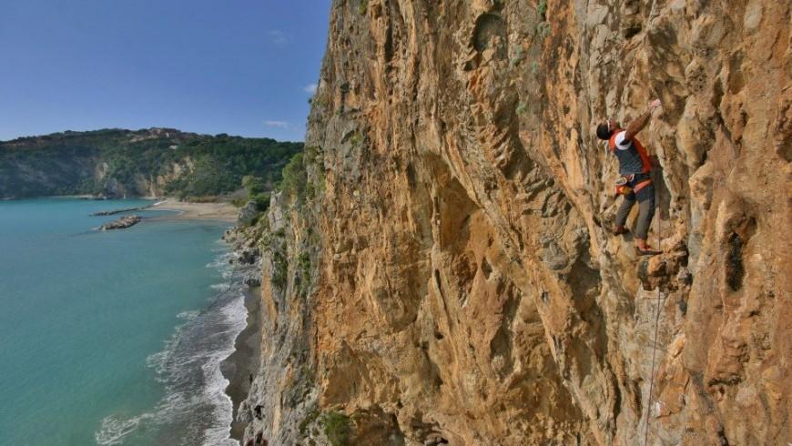 uno scalatore su una rossa parete verticale a picco sul mare