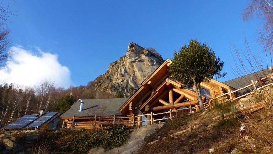 il rifugio in primo piano con dietro la rocca che spunta con la sua roccia chiara