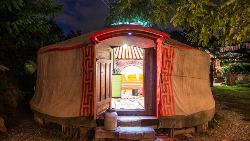 Yurta mongola, esterno di notte, immersa nel verde vicino a Torino