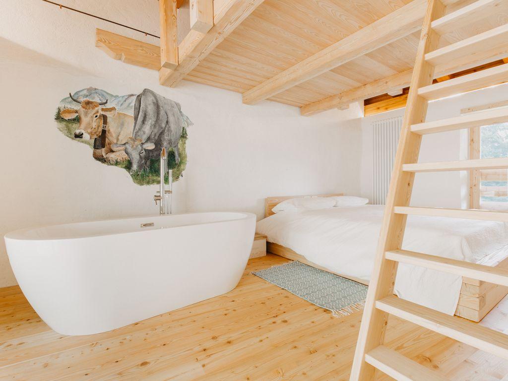 Una camera con vasca idromassaggio all'interno dello Chalet odomi maso nel bosco