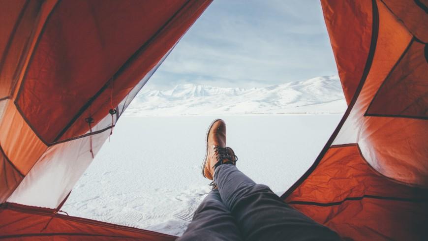 Persona comodamente distesa in tenda, foto di Colby Thomas, via Unsplash