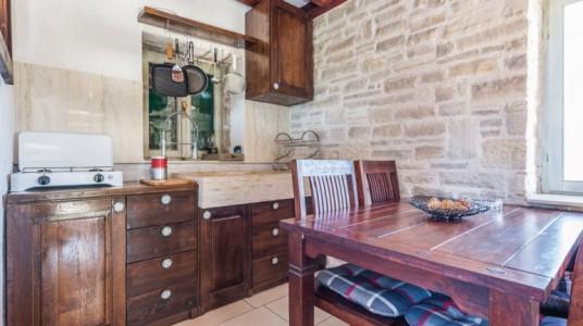 La cucina in legno e il lavello di pietra