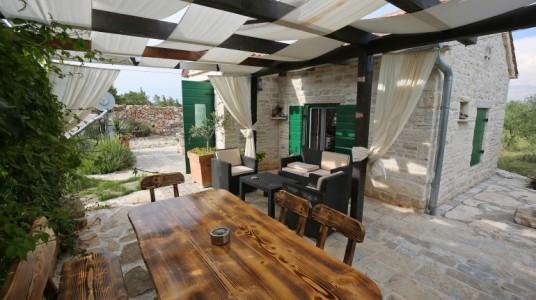 Esterno della casa, zona living con divanetto e poltrone e un tavolo da pranzo in legno, con le sedie. Una tettoia di legno con tende copre la zona