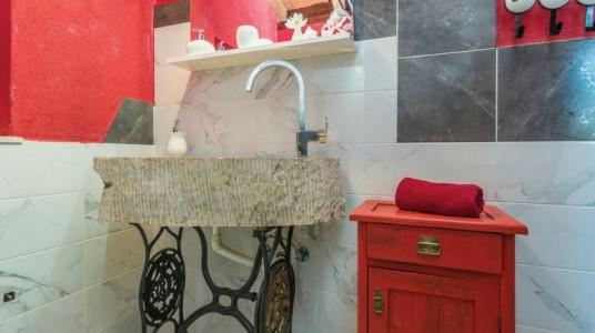 Dettaglio del bagno: il lavandino in pietra poggiato sul piede di un'antica macchina da cucire Singer, e un mobiletto in legno restaurato e dipinto di rosso