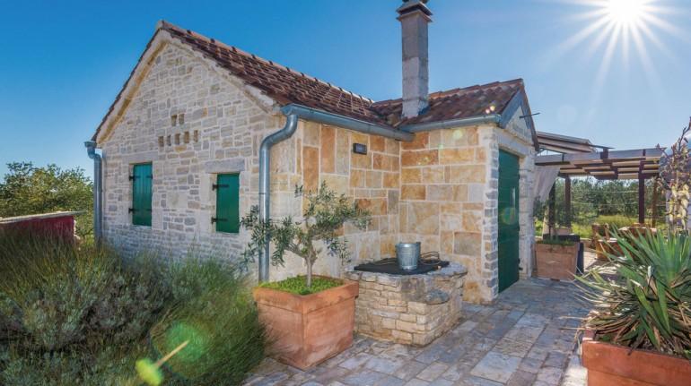 Esterno della casa, lato ingresso, con il pozzo-cisterna