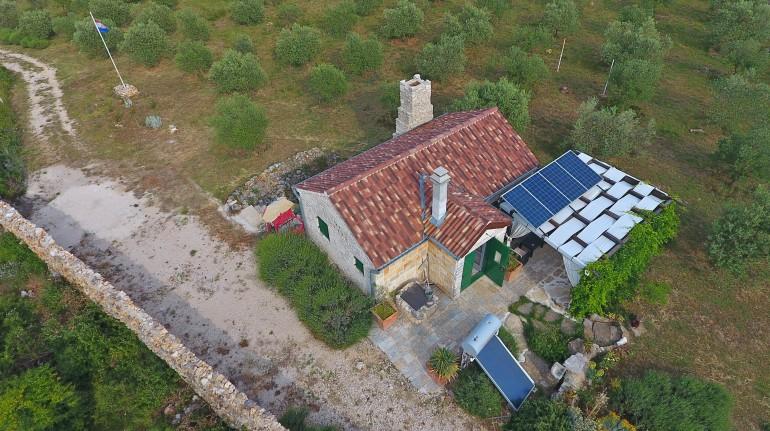 Vista aerea sulla casa, visibili il camino, i pannelli solari, l'impianto per il riscaldamento dell'acqua, il pozzo, la tettoia e gli ulivi