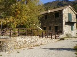 Esterno dell'Ecobnb Centro Anidra, in Liguria. Struttura in pietra, tetto a spiovente e staccionata