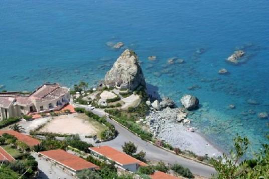 Vista aerea sulla cittdina di Amantea, affacciata sul Mar Tirreno, con l'acqua limpida e uno scoglio imponente attaccato alla costa