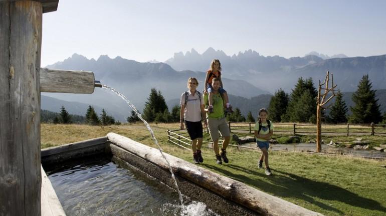Immagine di una famiglia, che passeggia su un prato verde, in montagna, vicino ad una fonte d'acqua