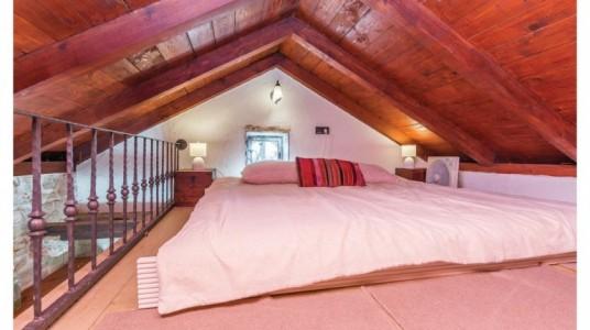 Letto matrimoniale sul soppalco. Il tetto di legno a spiovente e la finestra piccola e rotonda che illumina