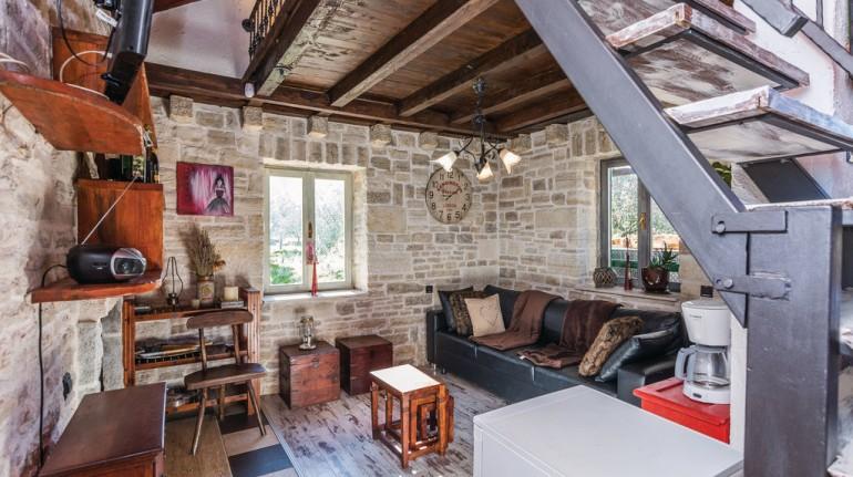 Salotto nell'open space, con arredi in legno, caminetto, scala che porta al soppalco e un grande divano