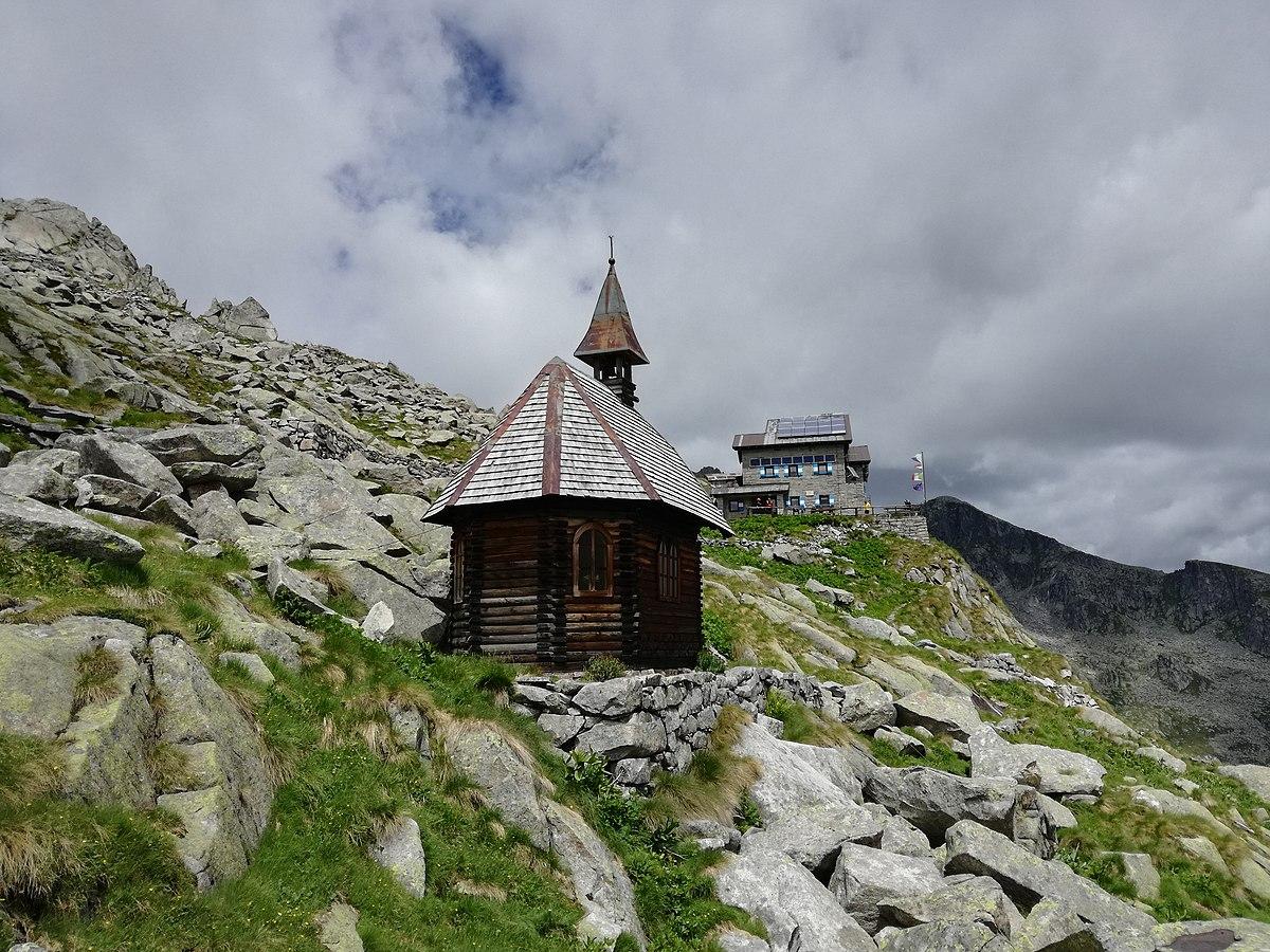 Una chiesetta alpina e sullo sfondo il rifugio Carè Alto, via Wikipedia commons