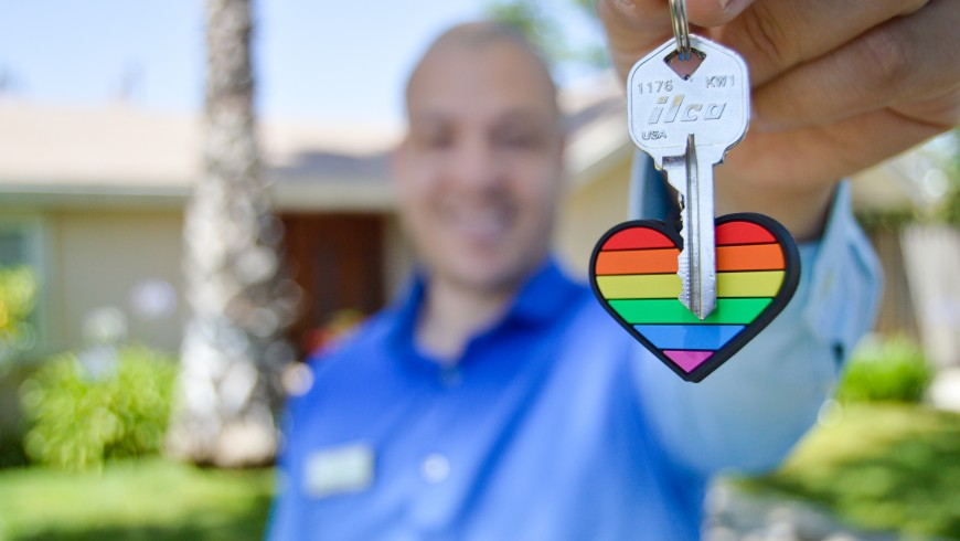 persona che tiene delle chiavi con un portachiavi a forma di cuore arcobaleno