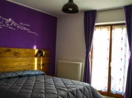 stanza con parete viola e arredi legno