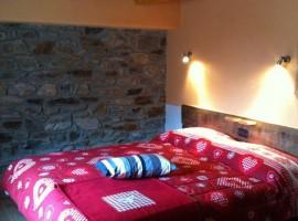 stanza con il muro in pietra e copriletto rosso