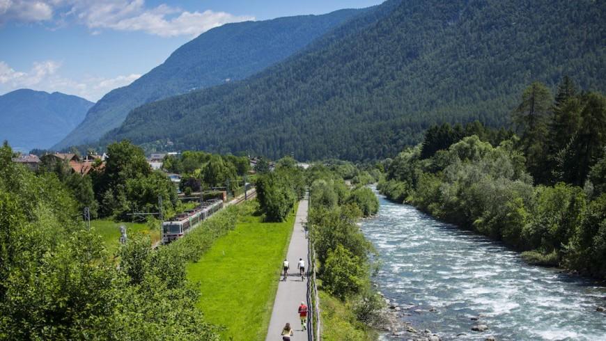 ciclabile con da una parte il treno e dall'altra il fiume noce