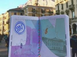 persona tiene in mano il passaporto con il timbro della città visitata