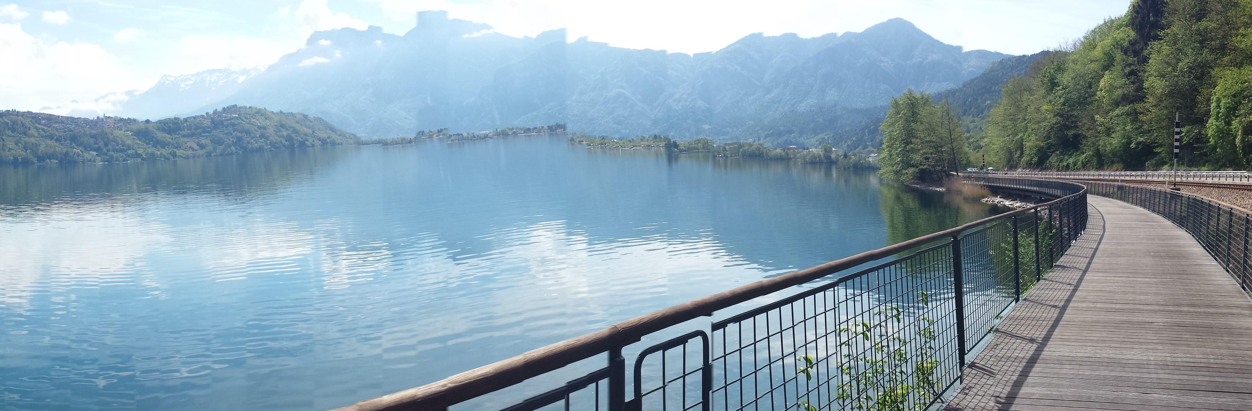 ciclabile sospesa sul lago con montagne sullo sfondo