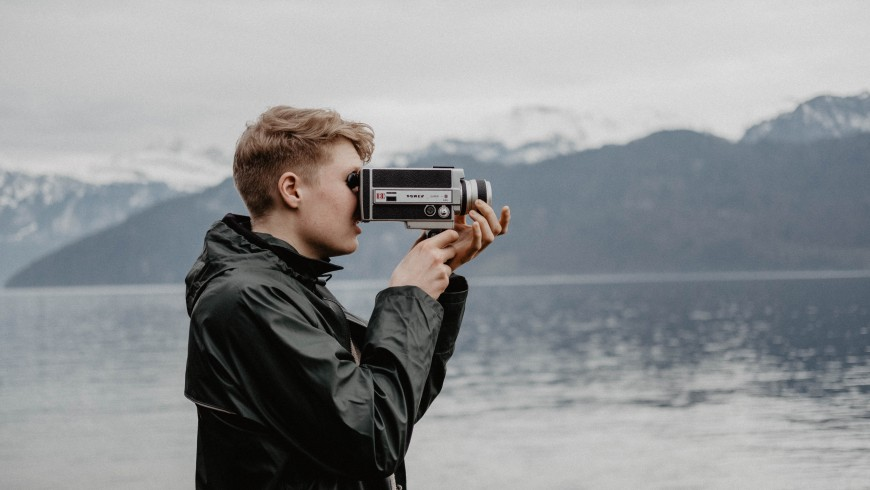 ragazzo con videocamera filma riva del lago viaggio lento