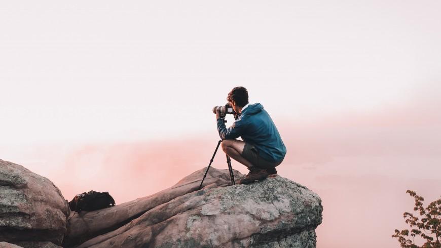 fotografo in montagna mette a fuoco il panorama