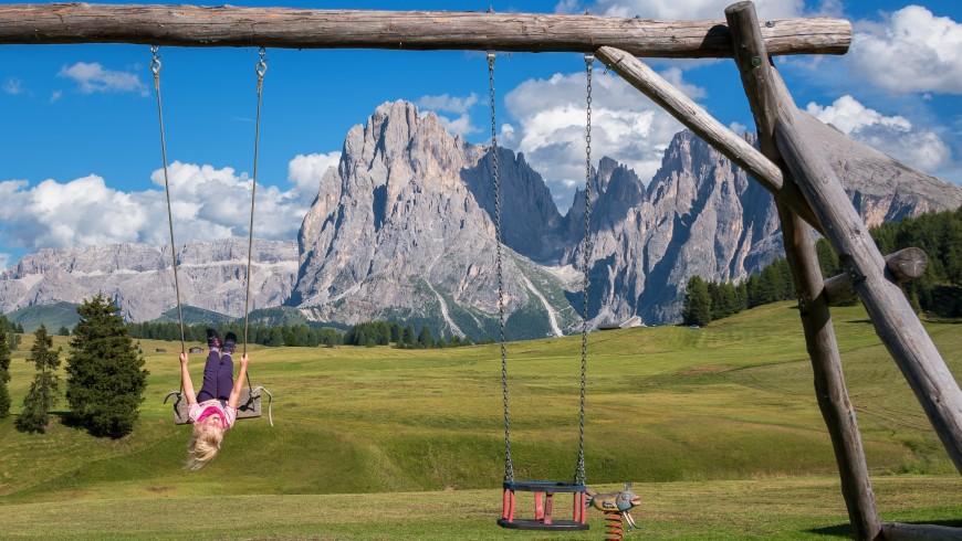 bambina che gioca in mezzo alla natura e alle montagne