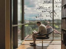 uomo accomodato su sedia leggendo libro e ammirando panorama