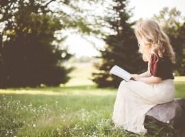 bambina leggendo libro nella natura