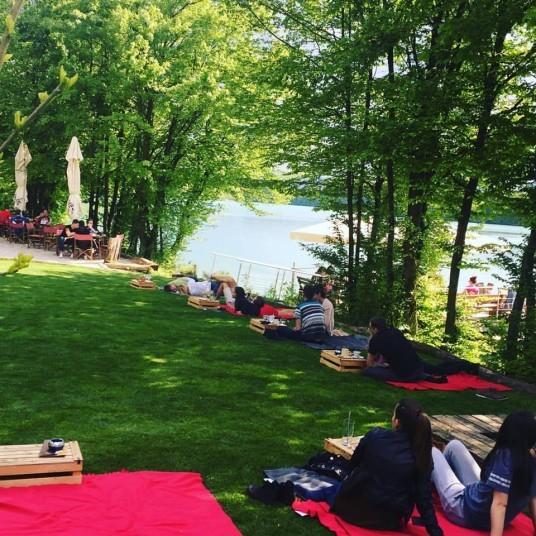 gente stesa sul prato del lago