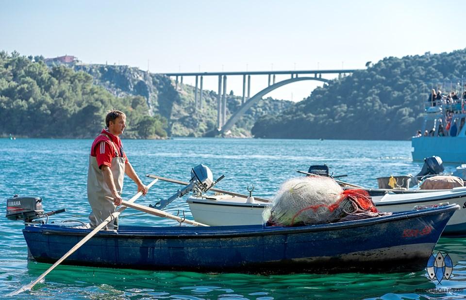 pescatore in riva al mare con la piccola imbarcazione