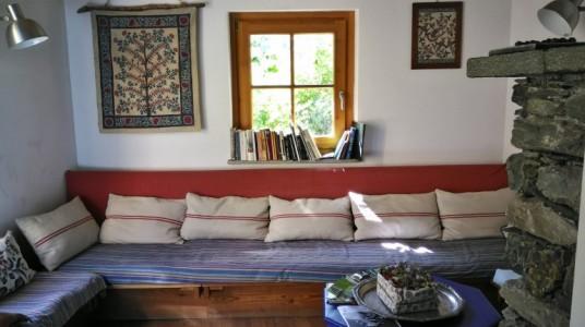 piccola sala di attesa con un divano e una finestra che dà sul giardino